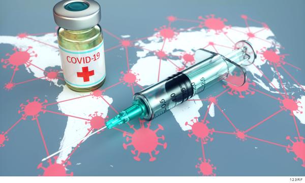 Imagen de una vacuna encima de un mapa del mundo