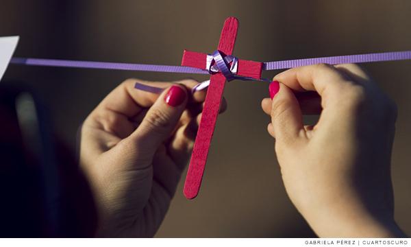Imagen de una mujer amarrando una cruz rosa con un listón morado en alusión a la violencia contra mujeres