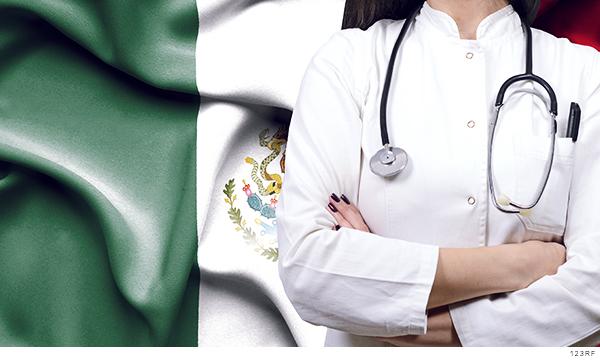 Fotografía del torso de una doctora, al fondo la bandera de México